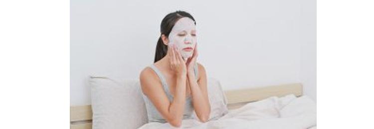 Woman apply facial mask on face